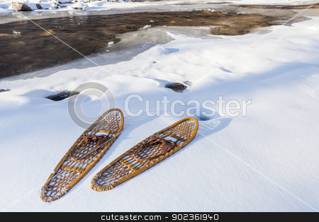 classic Bear Paw snowshoes stock photo, classic wooden Bear Paw snowshoes on the shore of partially frozen Cache la Poudre River near Fort Collins, Colorado by Marek Uliasz