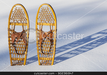 Bear Paw snowshoes stock photo, a pair of classic Bear Paw wooden snowshoes cast shadow in snow by Marek Uliasz