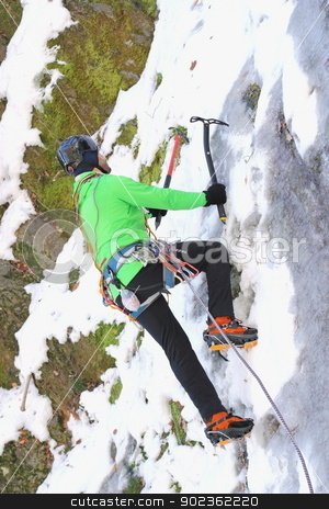 ice climbing in winter stock photo, man in green jumper climbing an ice wall  by coroiu octavian