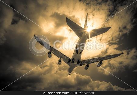 passenger jet stock photo, abstract of a large passenger jet landing through golden clouds by Steve Mann