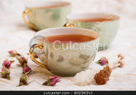 cup of tea  stock photo, Cup of tea with rose bud and rock sugar sticks by Grafvision