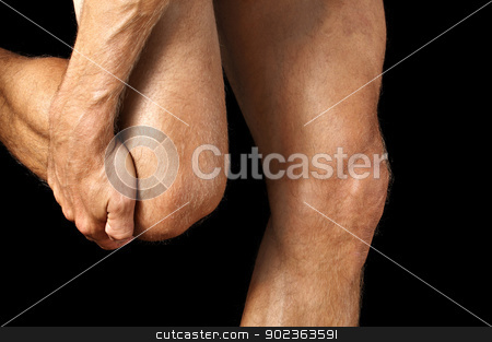 Knee pain stock photo, Closeup of man grasping his knee while walking on black background by Chad Zuber