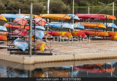 kayaks on a dock stock photo, colorful plastic recreational and sea kayaks on a floating dock with water reflections by Marek Uliasz