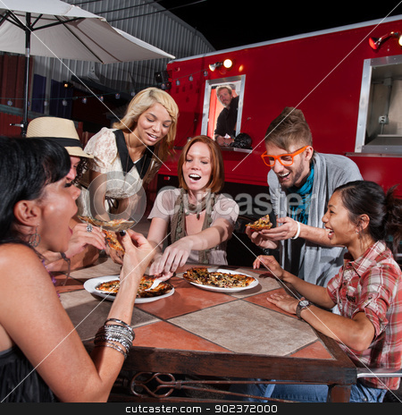 Laughing Group Eat at Canteen stock photo, Group of laughing people eating pizza at a food truck by Scott Griessel