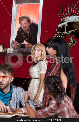 Young Woman with Chef at Food Truck stock photo, Smiling mulatto woman waiting at mobile pizza cafe next to chef by Scott Griessel