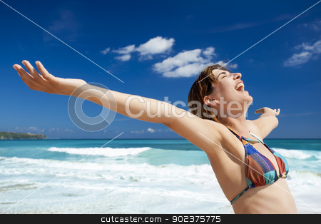 Enjoying the summer stock photo, Beautiful young woman with arms open in a tropical beach enjoying the summer  by ikostudio