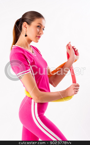 Pretty girl holding hula hoop stock photo, Young attractive woman with a hula hoop by Aikon