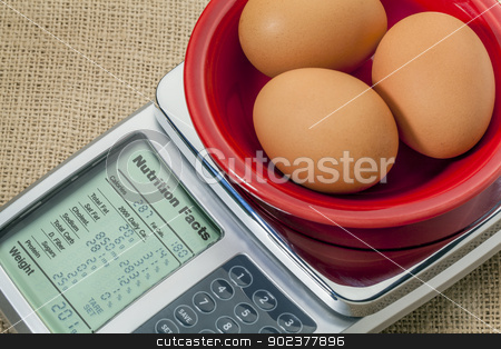 eggs on diet scale stock photo, three eggs on diet scale displaying nutrition facts - a diet concept by Marek Uliasz