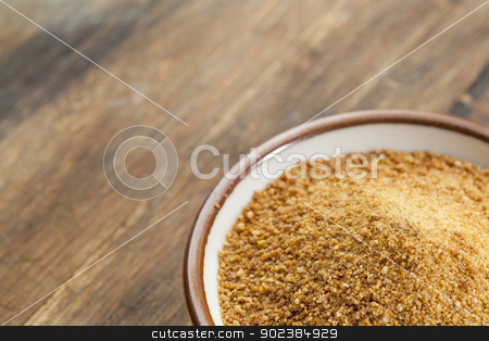 coconut palm sugar stock photo, small ceramic bowl of unrefined coconut palm sugar against an out of focus wood background - copy space by Marek Uliasz