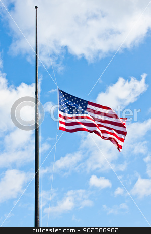Half staff American flag stock photo, American flag on a blue sky during a windy day by Paolo Gallo