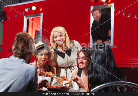 Happy People Eating By Canteen stock photo, Happy group of friends eating out by food truck by Scott Griessel