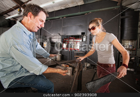 People Forming Glass Objects stock photo, Pair of artisans working at a glass company with tools by Scott Griessel