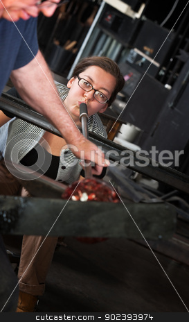Lady Using Blowpipe for Glass stock photo, Young glass maker blowing air through tube for glass object by Scott Griessel