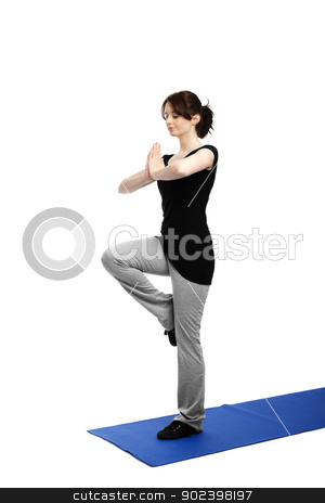 young woman exercising yoga on one leg on a blue mat stock photo, young woman exercising yoga on one leg on a blue mat by Rob Stark