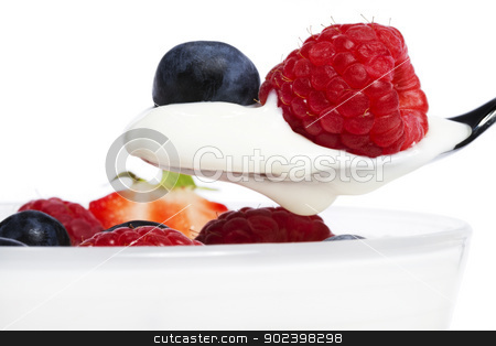raspberry and blueberry on a spoon with yogurt in front of a dessert on white background stock photo, raspberry and blueberry on a spoon with yogurt in front of a dessert on white background by Rob Stark