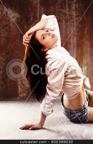 young woman sitting on wooden floor in front of a rusty background stock photo, young woman sitting on wooden floor in front of a rusty background by Rob Stark