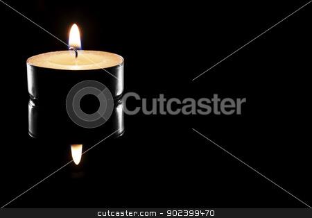 one burning tea candle on black reflective background stock photo, one burning tea candle on black reflective background by Rob Stark
