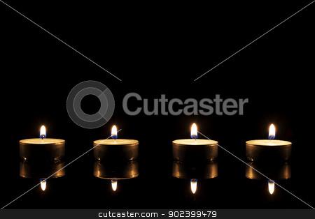 four burning tea candles on a black mirror on black background stock photo, four burning tea candles on a black mirror on black background by Rob Stark