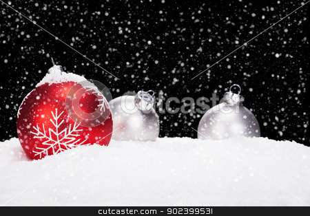 red and silver christmas balls in snow on black background while snowing stock photo, red and silver christmas balls in snow on black background while snowing by Rob Stark