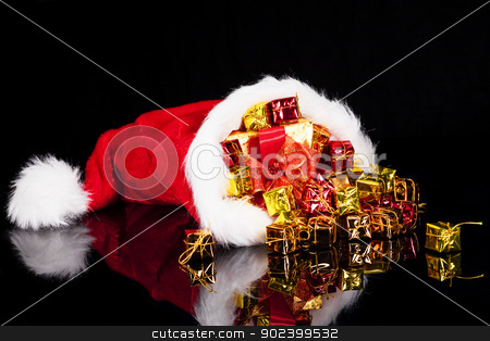 christmas gifts falling from santa's hat on black background stock photo, christmas gifts falling from santa's hat on black background by Rob Stark