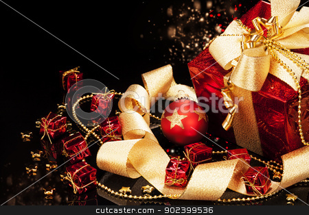 red christmas present with a red christmas ball and ribbons on black background stock photo, red christmas present with a red christmas ball and ribbons on black background by Rob Stark