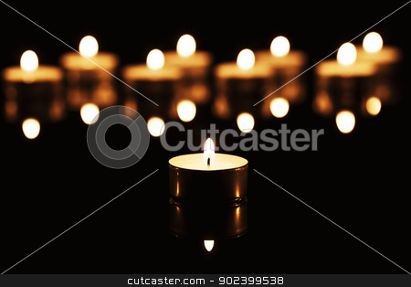 one burning tea candle in front of many burning tea candles on a black mirror stock photo, one burning tea candle in front of many burning tea candles on a black mirror by Rob Stark