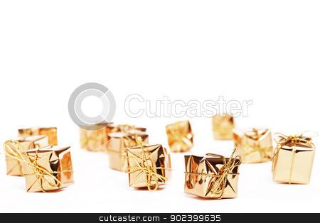 tiny golden christmas presents on white background stock photo, tiny golden christmas presents on white background by Rob Stark