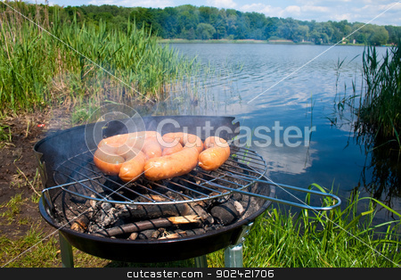 Grilling at summer weekend stock photo, Fresh sausage preparing on grill at the lakeshore by Jan Remisiewicz