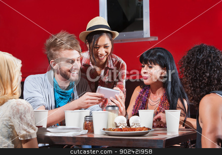 Diverse Group Eating and Texting stock photo, Group of diverse people laughing with phone and eating pizza by Scott Griessel