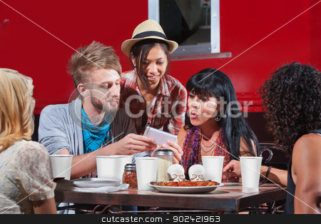 Friends Eating and Looking at Phone stock photo, Group of friends eating out and looking at smartphone by Scott Griessel