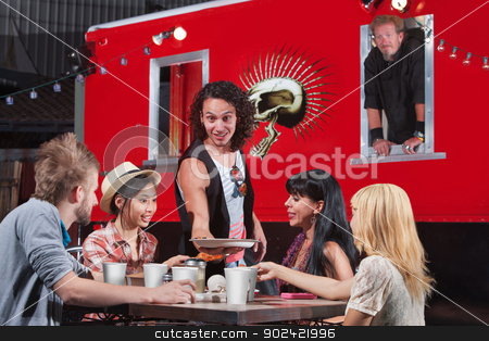 Food Truck Pizza Delivery stock photo, Handsome man bringing plate of food to group of diners at food truck by Scott Griessel