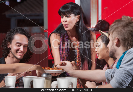 Mature Woman Serving Pizza stock photo, Cute mature woman sharing pizza with young group by Scott Griessel