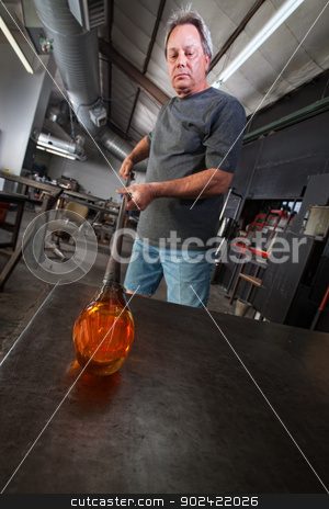 Serious Glass Artisan stock photo, Serious worker with molten glass object on workbench by Scott Griessel