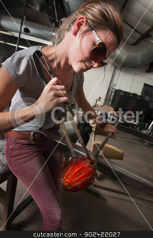 Lady Working with Hot Glass stock photo, Young woman working hot glass vase with iron tools by Scott Griessel