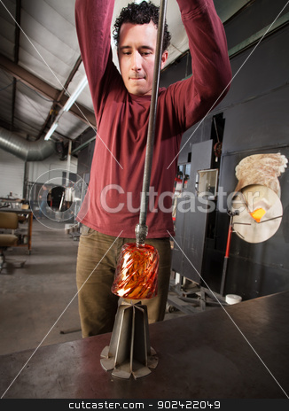 Artist Pulling Glass from Die stock photo, Young industrial artist pulling hot glass from iron die by Scott Griessel
