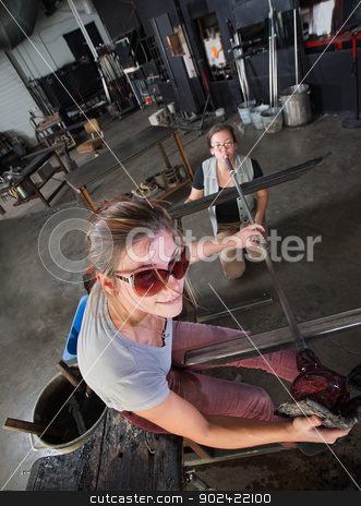 Smiling Glass Artisan stock photo, Cheerful Caucasian glass artist with assistant and orange vase by Scott Griessel