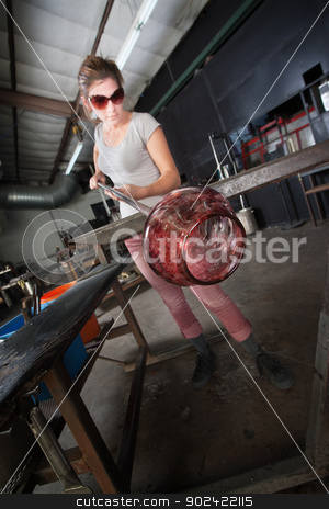 Artist Making a Glass Jar stock photo, Young European glass artisan holding hot vase with rod by Scott Griessel