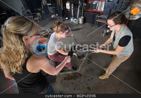 Three Artists Working with Glass Jar stock photo, Trio of young white women working on glass art creation by Scott Griessel
