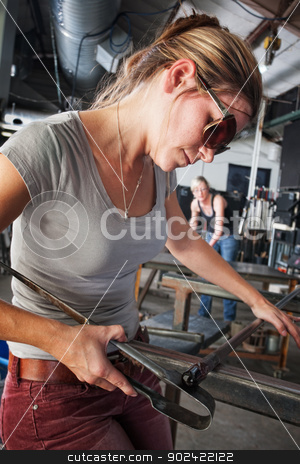 Sculptor Shaping Glass Art stock photo, Pretty glass sculptor shaping tiny object on workbench by Scott Griessel