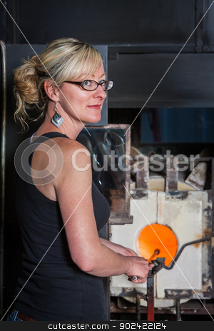 Lady Working Near Kiln stock photo, Smiling blond woman holding rod in hot blast furnace by Scott Griessel