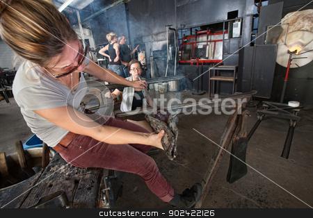 Cooling Hot Glass with Mitt stock photo, Industrial craft artists cooling hot glass art object by Scott Griessel