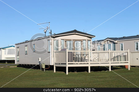 Caravan park stock photo, Modern static caravans in park with blue sky background. by Martin Crowdy