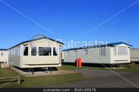 Caravan trailer park stock photo, Caravans parked in modern trailer park with blue sky background. by Martin Crowdy