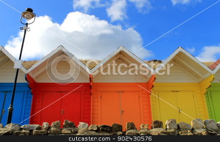 Colorful beach chalets stock photo, Row of colorful beach chalets with blue sky background. by Martin Crowdy