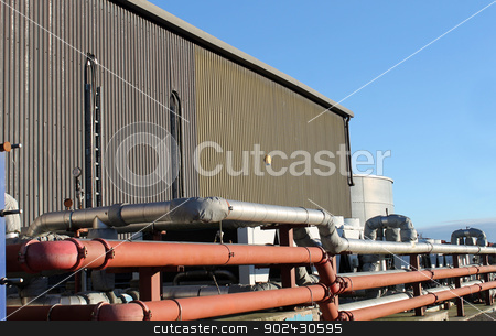 Factory building exterior stock photo, Pipes on exterior of modern factory building. by Martin Crowdy