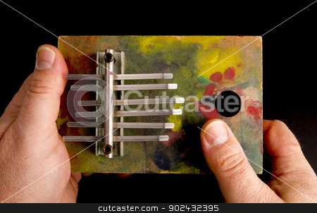 Hands Playing Tune on Musical Instrument of the Thumb Harp stock photo, Hands Playing Tune on Musical Instrument of the Thumb Harp by Christopher Boswell