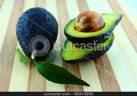 Avocados stock photo, Black Ripe Avocados with leaves on wood Background. by Designsstock