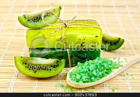 Soap homemade and salt in a spoon with kiwi stock photo, Two green homemade soap, salt on a wooden spoon, kiwi slices on a bamboo mat by rezkrr