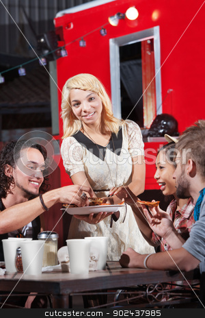 Friends Eating Out at Restaurant stock photo, Laughing group of friends eating out at pizza restaurant by Scott Griessel