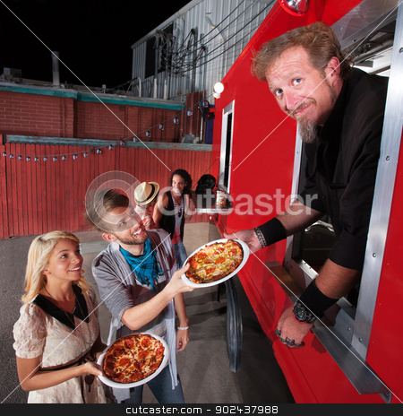 Pizza Dinner at Food Truck stock photo, Food truck owner serving pizza to happy couple by Scott Griessel